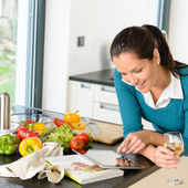 Smiling woman searching recipe tablet kitchen vegetables — Stok fotoğraf