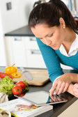 Woman looking tablet reading recipe kitchen vegetables — Foto Stock