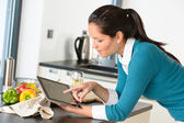 Young woman reading recipe tablet kitchen searching — Stock Photo