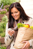 Smiling woman shopping vegetables mobile phone sms — Stock Photo