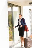 Smiling woman business flight attendant arriving home — Stock Photo