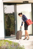 Businesswoman leaving house traveling carrying baggage hurried — Stock Photo