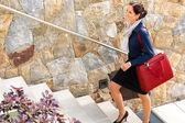 微笑的女人攀爬楼梯的行李旅行到达 — 图库照片