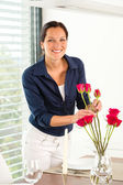 Young woman arranging flowers dinner table — Stock Photo