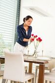 Woman decorating red roses dining room wife — Stock Photo