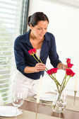 Young woman arranging flowers dinner table — Stok fotoğraf