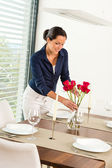 Young woman placing flowers dinner table — Stok fotoğraf