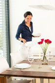 Pretty woman setting table dining room preparing — Stock Photo