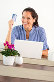 Smiling woman shopping online home credit card — Stock Photo