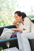 Woman eating sandwich lunch breakfast home sofa — Stock Photo