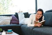 Ung kvinna liggande läsande bok soffa soffa — Stockfoto