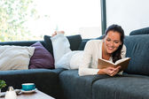 Young woman lying reading book couch sofa — Stok fotoğraf