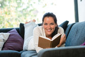 Smiling woman resting reading sofa learning domestic — Stock Photo