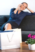 Smiling businesswoman talking cell phone bags home — Stock Photo