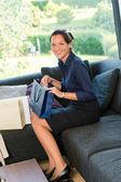 Młody uśmiechający się torby na zakupy kobieta siedzi na kanapie — Zdjęcie stockowe