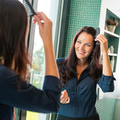 Young woman combing hair comb mirror bathroom — Stock Photo