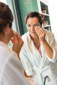 Young woman cleaning face cotton pads bathrobe — Stock Photo