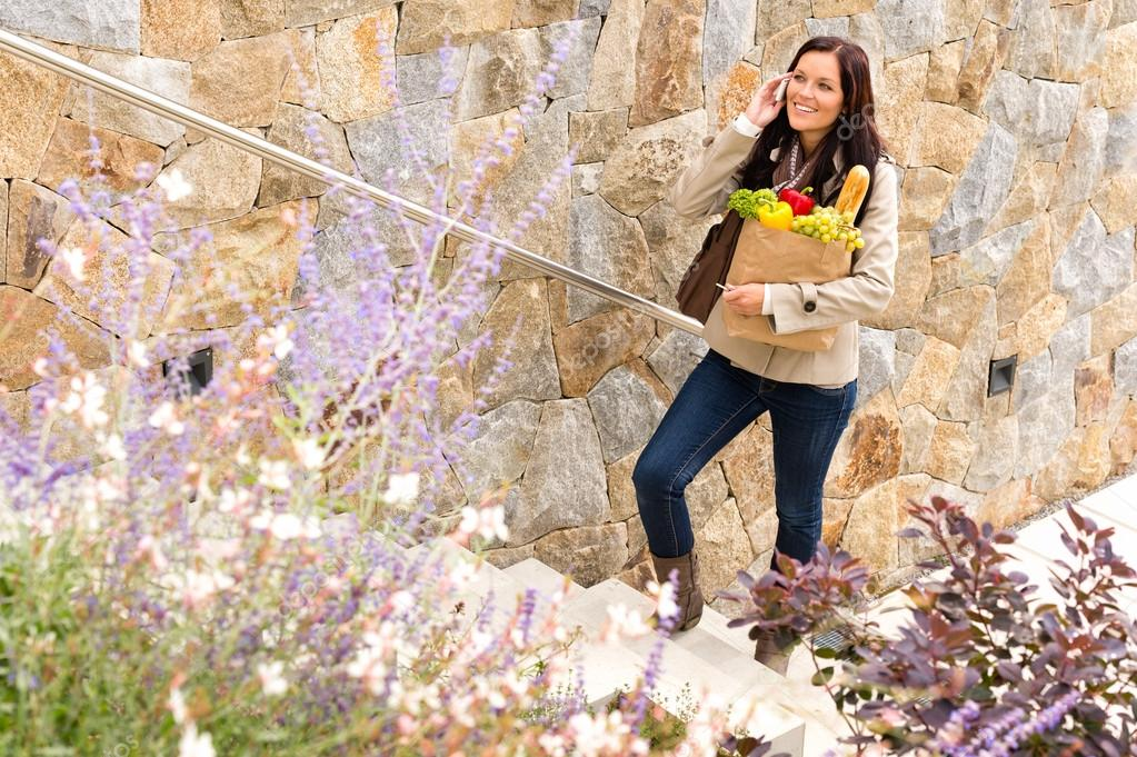 Smiling woman climbing stairs talking phone shopping bag groceries — Stock Photo #19055309