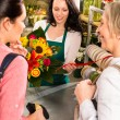 Happy women customers buying flowers sunflower bouquet - Stok fotoğraf