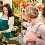 Young florist preparing cut flowers shop buyers — Stock Photo