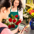 Woman florist selling flowers customer paying card — Stock Photo #19857703