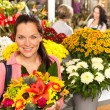 Cheerful florist woman showing colorful flowers market - Stock Photo