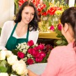 Happy florist making roses bouquet women customer - Stok fotoraf
