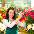 Happy young woman arranging flowers florist shop — Stock Photo #19857743