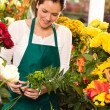 Young florist preparing flowers bouquet shop store — Stock Photo #19857749