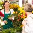 Young woman arranging flowers shop market selling — Stock Photo #19857761