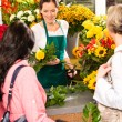Young woman florist cutting flower shop customers — Stock Photo