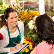 Happy florist writing flower shop talking customer — Stock Photo #19857789