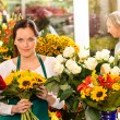 Woman florist selling sunflowers bouquet flower shop - Stok fotoraf