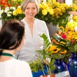 Senior woman buying plant paying flower market — Stock Photo