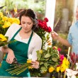 Woman florist cutting flowers shop bouquet man — Stock Photo