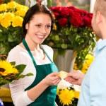 Smiling florist man customer buying flowers card — Stock Photo