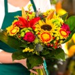 Florist holding bouquet colorful flowers shop assistant — Stock Photo