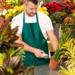 Florist man reading barcode potted plant shop - Stock Photo