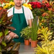 Young man scanning barcode flower shop gardening — Stock Photo #19857867