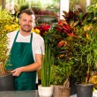 Male shop assistant potted plant flower working — Stockfoto