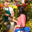 Man selling pot woman customer flower shop - ストック写真