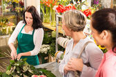 Young florist preparing cut flowers shop buyers — Stock Photo