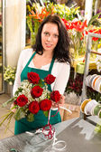 Florist woman arranging flowers roses shop working — Stock Photo