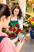 Woman florist selling flowers customer paying card — Stock Photo