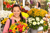 Cheerful florist woman showing colorful flowers market — Stock Photo