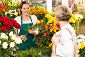 Young woman arranging flowers shop market selling — Stock Photo