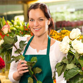Smiling florist cutting rose flower shop woman — Stock Photo