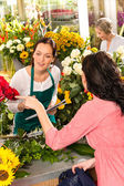 Young florist ordering roses woman customer flower — Stock Photo