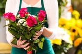 Florist hands showing red roses bouquet flowers — Stock Photo
