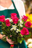 Florist woman holding red roses bouquet hands — Stock Photo